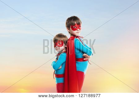 Little boys in the cloaks. Children on sunset sky background. Power concept.