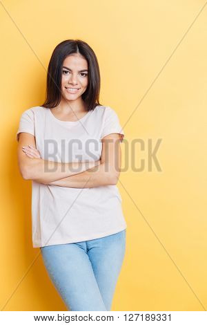 Happy lovely woman standing with arms folded over yellow background