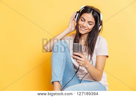 Smiling woman listening music in headphones and using smartphone over yellow background