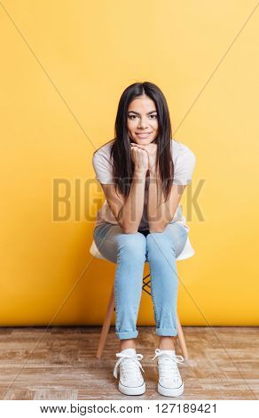 Happy casual woman sitting on the chair over yellow backgorund