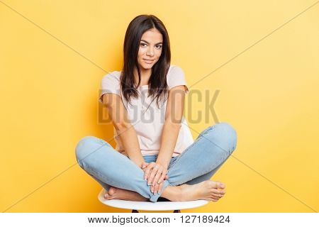 Happy cute woman sitting on the chair and looking at camera over yellow background