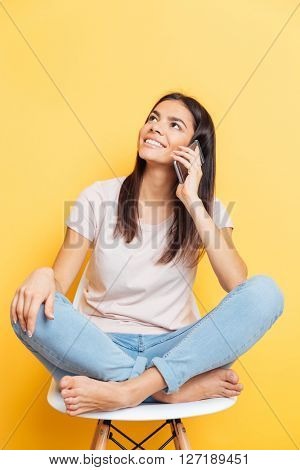 Happy woman talking on the phone and looking up over yellow background