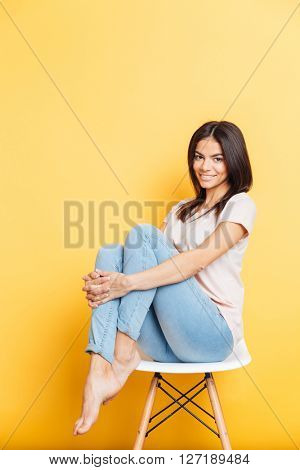 Smiling attractive woman sitting on the chair over yellow background