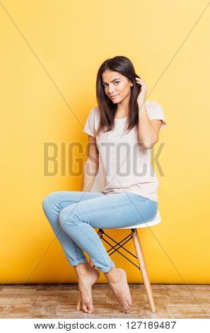 Pretty young woman sitting on the chair over yellow background