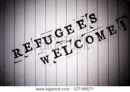 refugees welcome text on white line paper