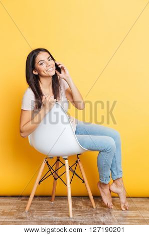 Smiling pretty woman sitting on the chair and talking on the phone over yellow background