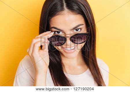 Smiling woman in sunglasses looking at camera over yellow background