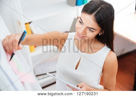 Smiling businesswoman writing on whiteboard in office