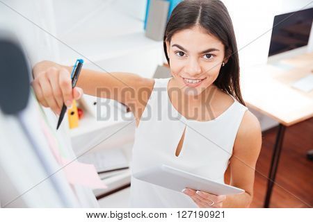 Happy businesswoman holding tablet computer and writing on whiteboard in office