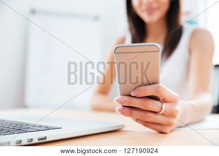 Closeup portrait of a female hands using smartphone in office. Focus on smartphone