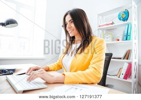 Happy young businesswoman using keyboard and computer mouse in office