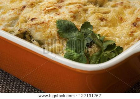 Cannelloni with spinach and ricotta baked in sauce bechamel in a pan