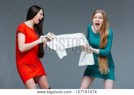 Two pretty angry young women with long hair quarreling and fighting for white dress over grey background