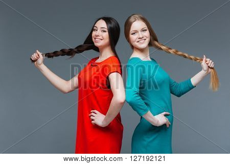 Two cheerful attractive young women with dark and fair hair showing their long braids over grey background