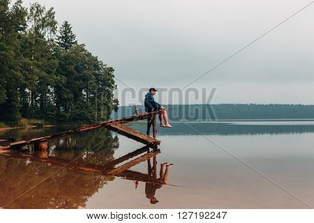 Man sits on a wooden bridge waits when the fish are biting. Weekend photo. ** Note: Visible grain at 100%, best at smaller sizes
