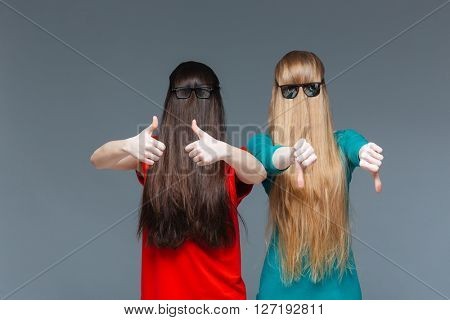 Two comical young women with faces covered by long hair showing thumbs up and thumbs down over grey background