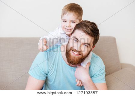 Portrait of happy father and son sitting on sofa at home together