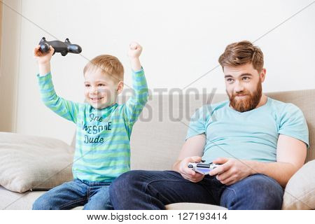 Cheerful excited little son playing computer games with father and winning