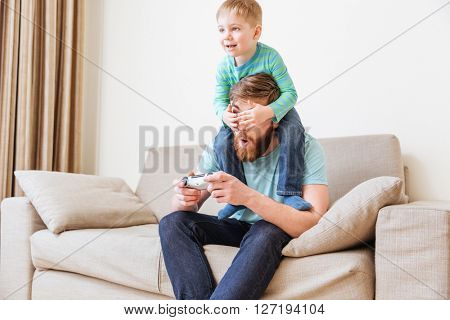 Smiling little boy covering eyes of his father while he playing computer games on sofa at home