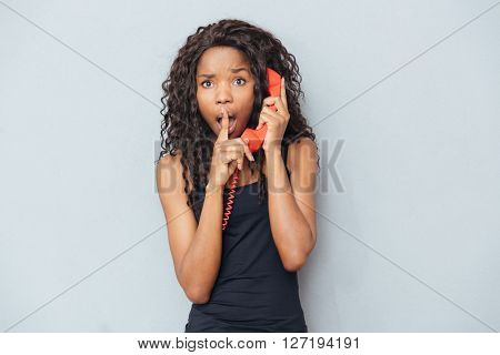 Afro american woman talking on retro phone tube and showing finger over lips over gray background