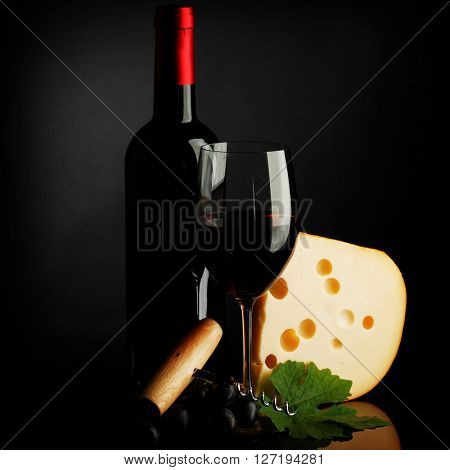 Red wine bottle, glass, cheese and corkscrew on dark background