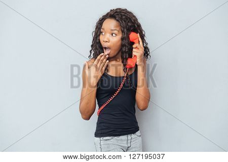 Amazed woman talking on retro phone tube and looking away over gray background