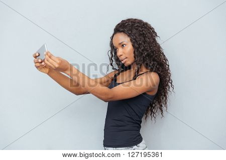 Afro american woman making selfie photo on smartphone over gray background