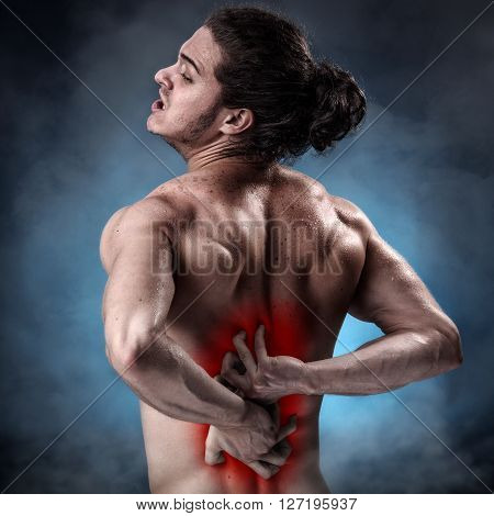 Handsome young man with lower back pain colored in red