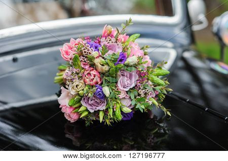 Elegant bridal bouquet of different flowers on the hood of a black retro car. Lacquered surface reflection.