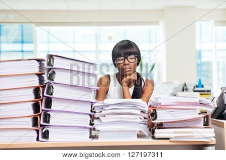 Sad afro american businesswoman sitting at the table with many work in office