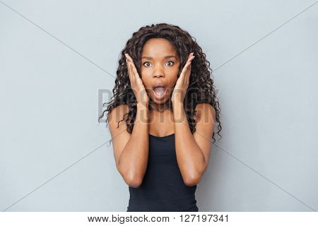 Amazed afro american woman looking at camera over gray background