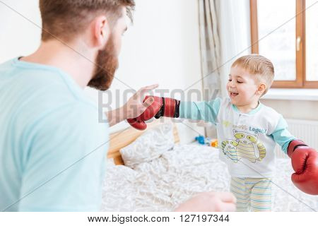 Bearded young father playing with his little son in boxing gloves at home