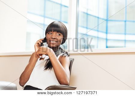 Smiling businesswoman talking on the phone in office and looking away