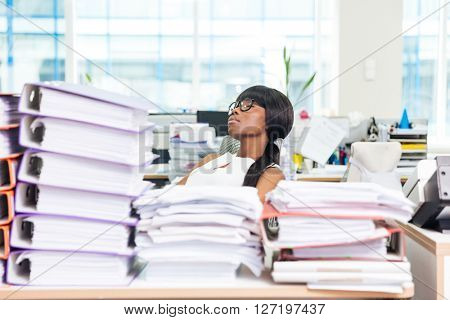 Afro american businesswoman sleeping in office with many work