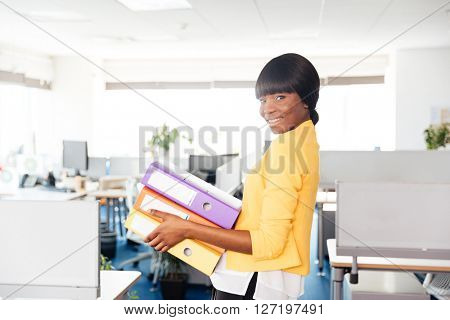 Happy afro american businesswoman holding folders and looking at camera in office