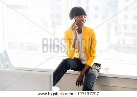 Happy afro american businesswoman talking on the phone in office