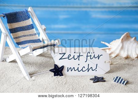 Summer Label With German Text Zeit Fuer Mich Means Time For Me. Blue Wooden Background. Card With Holiday Greetings. Beach Vacation Symbolized By Sand, Deck Chair And Shell.