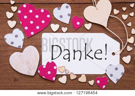 Label With Pink Textile Hearts On Wooden Background. German Text Danke Means Thank You. Retro Or Vintage Style