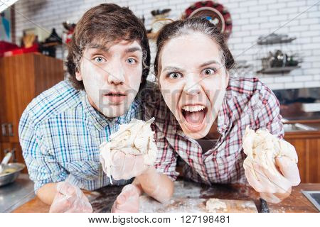 Comical angry young couple with flour on their faces holding dough and shouting