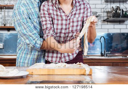Beautiful young couple kneading dough and hugging on the kitchen