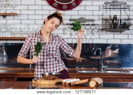 Happy beautiful young woman with dill and parsley dacing on the kithen