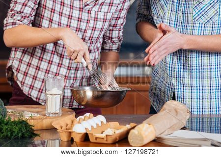 Closeup of young couple beating eggs and cooking omelette on the kitchen