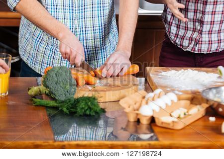 Hands of young couple cooking and cutting carrots on the kitchen