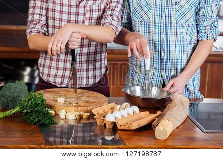 Young couple in checkered shirts cooking together on the kitchen