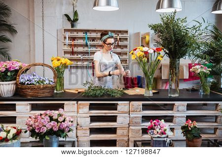 Cute concentrated young female florist in glasses working in flower shop