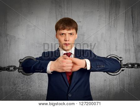 Businessman with several sections of huge chain