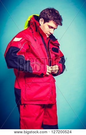 Young male getting dressed. Man putting on waterproof clothes. Adventure danger outdoors concept.