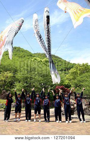 KAGAWA, JAPAN - MAY 22, 2016: Excursion of an Japanese high school girls, they are poseing pleasant and fun in a row at Fudonotaki- park, Kagawa, Japan.