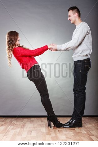 Happy couple holding each other's hands. Two lovers looking in the eye. Good relationship. Love and togetherness concept. Studio shot.