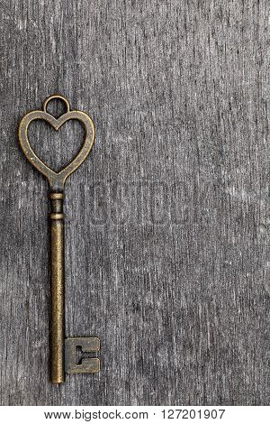 heart shaped vintage key on grunge wooden background